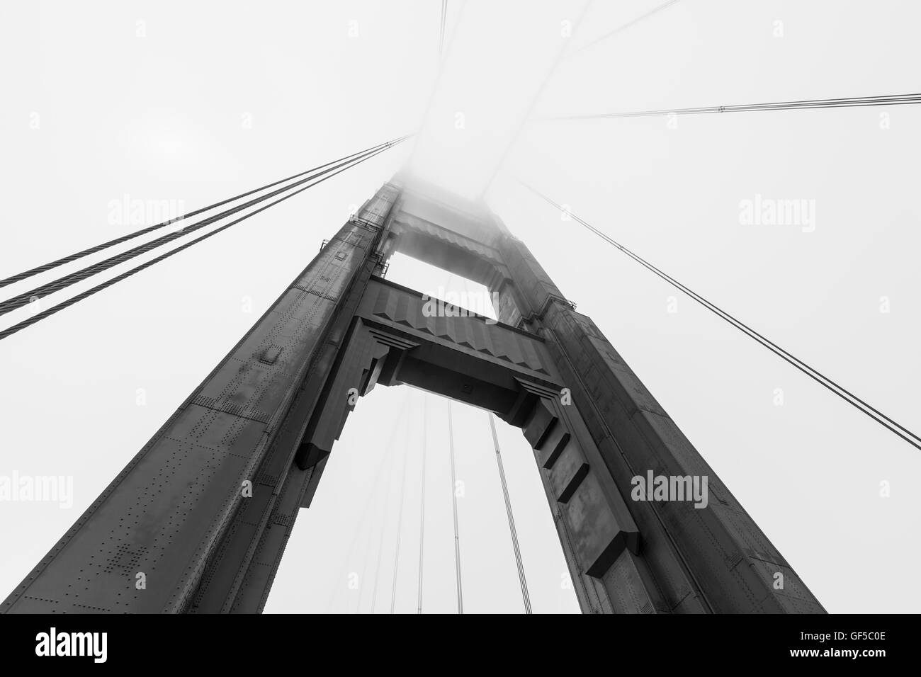 Golden Gate bridge tower emerging from iconic San Francisco bay fog bank in black and white. - Stock Image