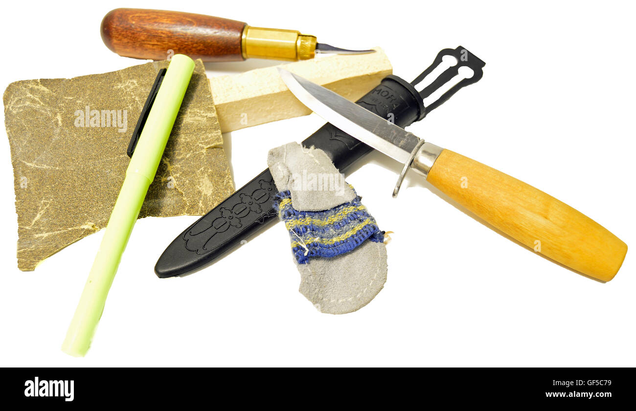 Group of carving supplies: two carving knife and sheath, sandpaper, yellow highlighter, and block of wood on a white - Stock Image