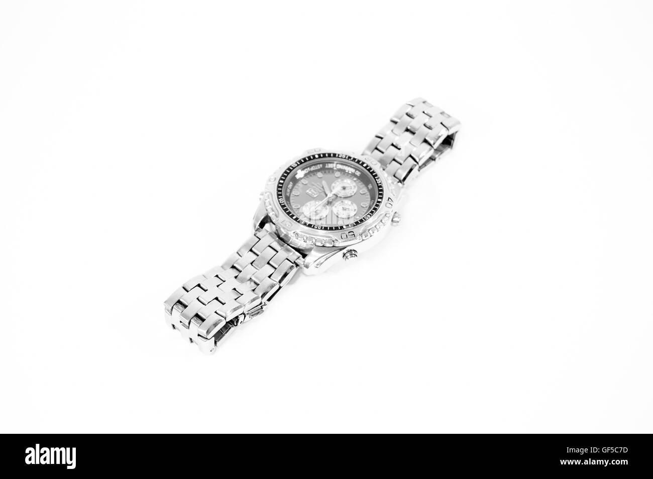 A silver and black watch with four buttons and three dials on a white background. - Stock Image