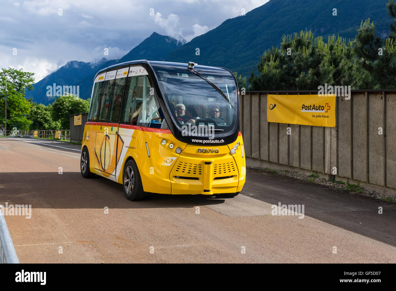 Autonomously driving electric minibus NAVYA ARMA in yellow livery operated by Postauto in Switzerland under the - Stock Image