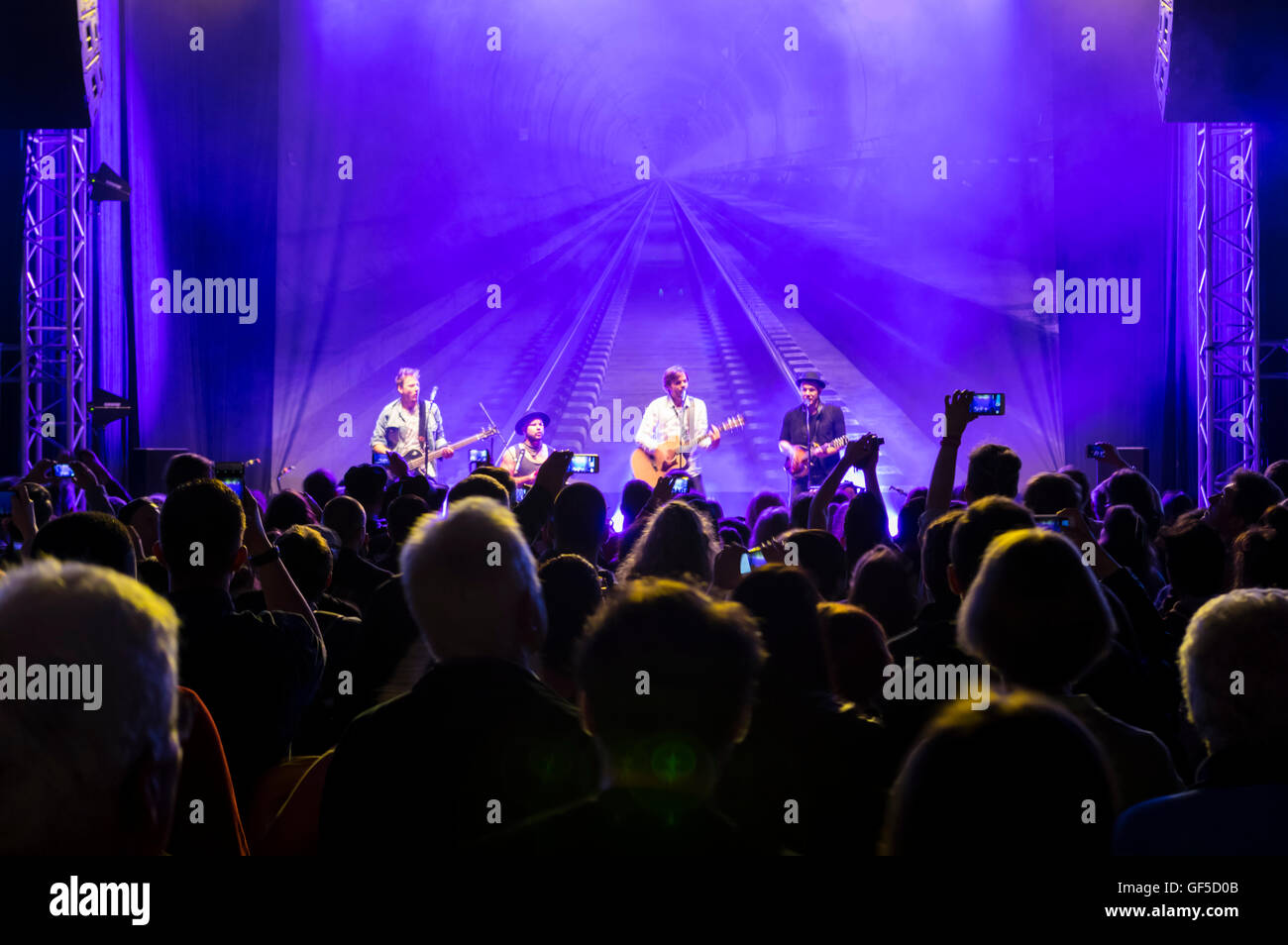 People taking mobile phone pictures of the Swiss folk rock group 77 Bombay Street performing at a concert. - Stock Image