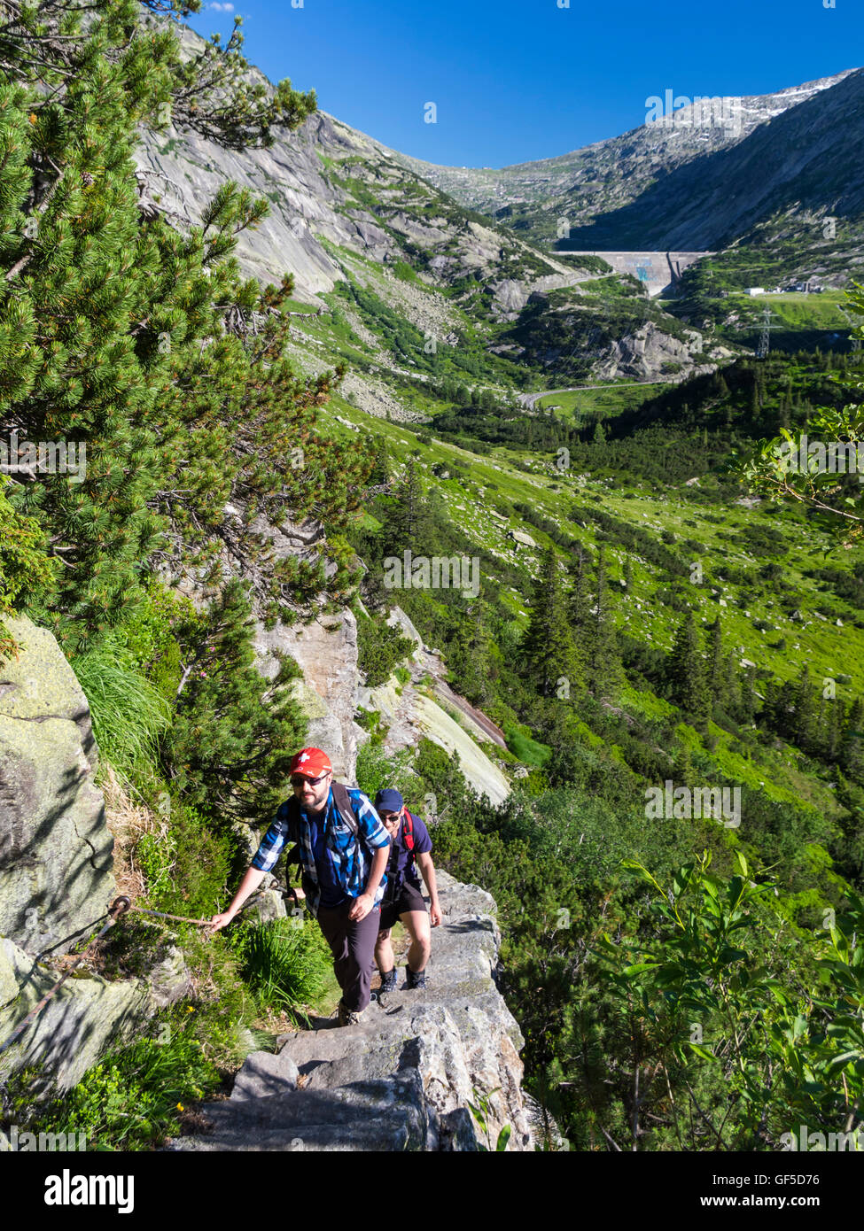 Two male hikers in the Grimsel region of the Swiss Alps, ascending on an exposed and steep stair-like trail. - Stock Image