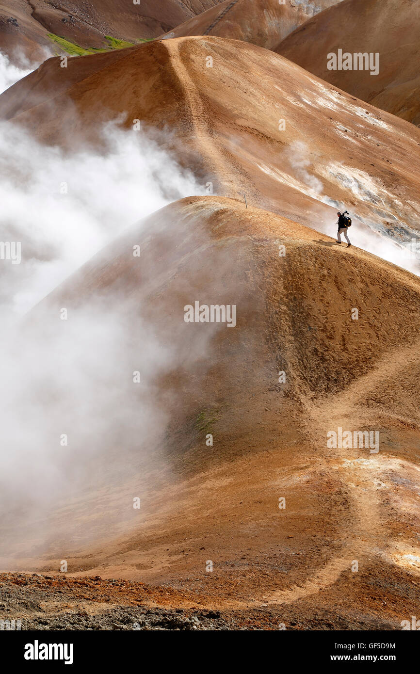 Rhyolite mountain, fumaroles and hiker on trail, Kerlingarfjoll, Iceland - Stock Image