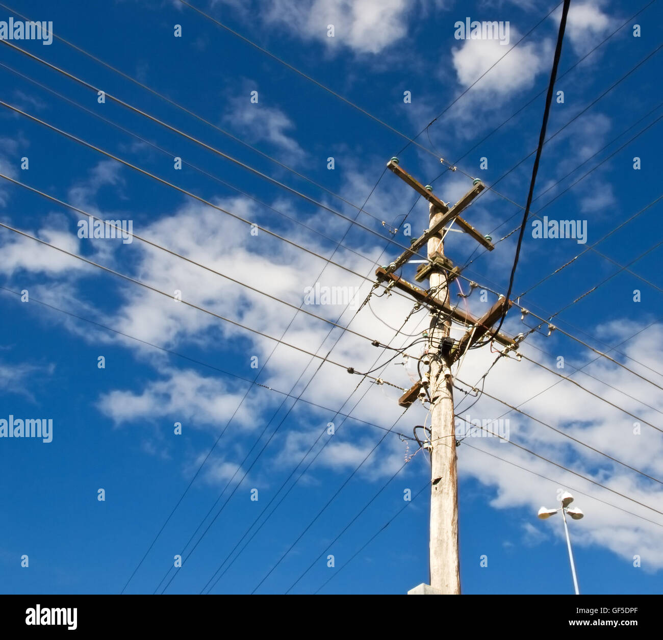 power lines for australian power pole electricity grid against cloudy blue sky - Stock Image