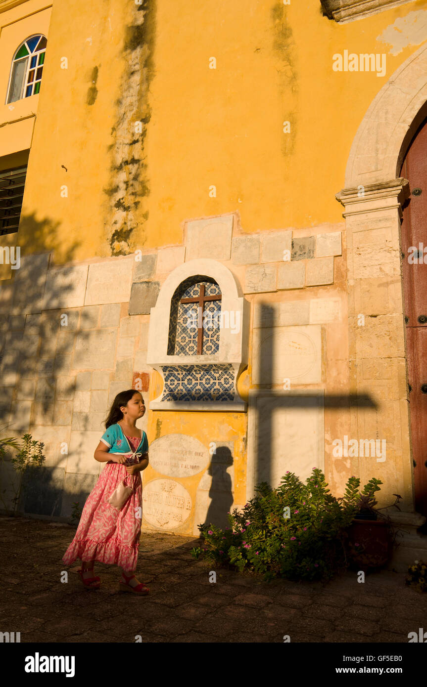 Young girl with cross walks in front of church in downtown Campeche during a trip through southern Mexico. Stock Photo
