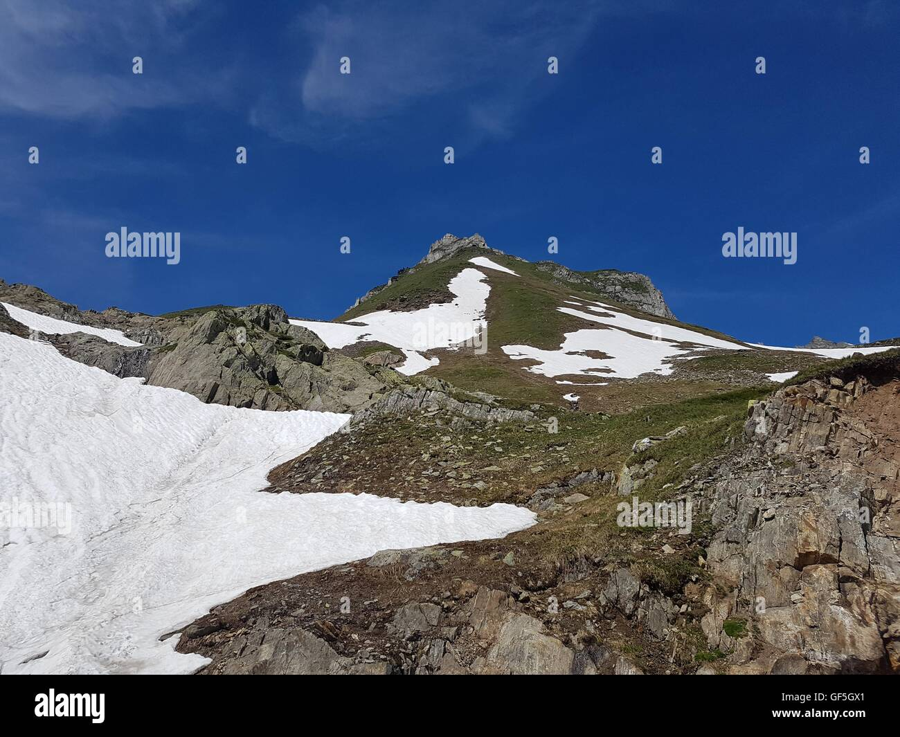 Heading to the summit in high mountain landscape in the Alps in the summer - Stock Image