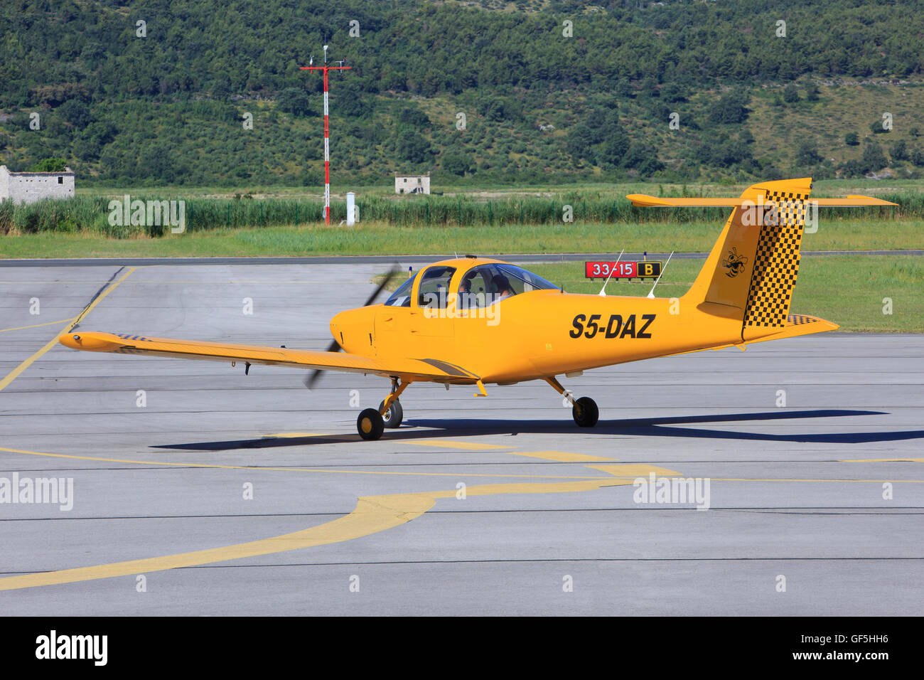 Yellow airplane taxiing down the runway at Portoroz Airport in Secovlje, Slovenia - Stock Image