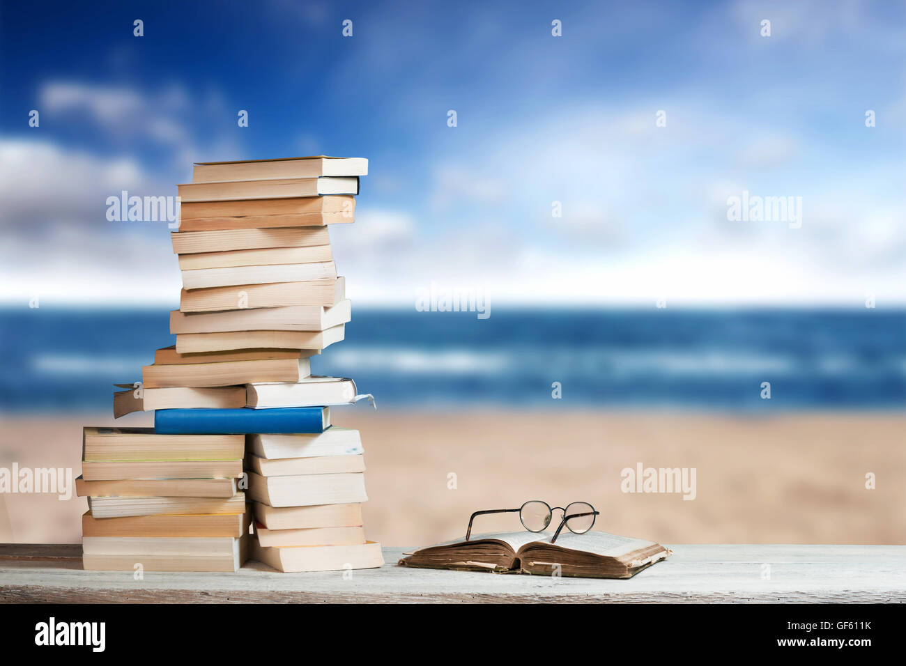 Stack of Travel Guides before a Beach - Stock Image