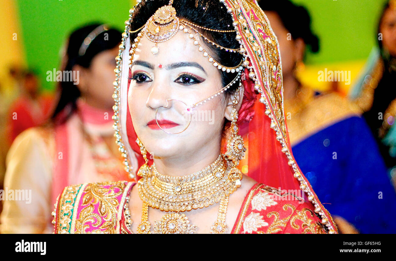 portrait of Indian bride wearing gold jewelry and red wedding