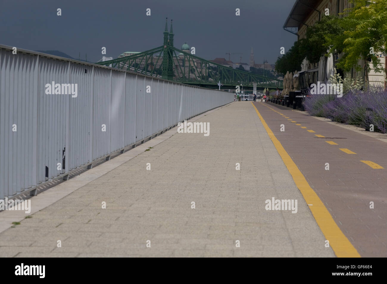 Walkway and cycleway beside eastern bank of Danube with threatening cloud in distance - Stock Image