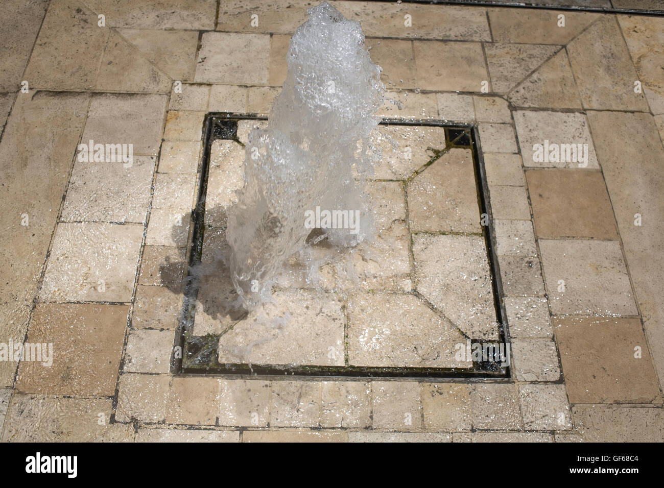 water gushing out of drain cover on hot summer day in city centre - Stock Image