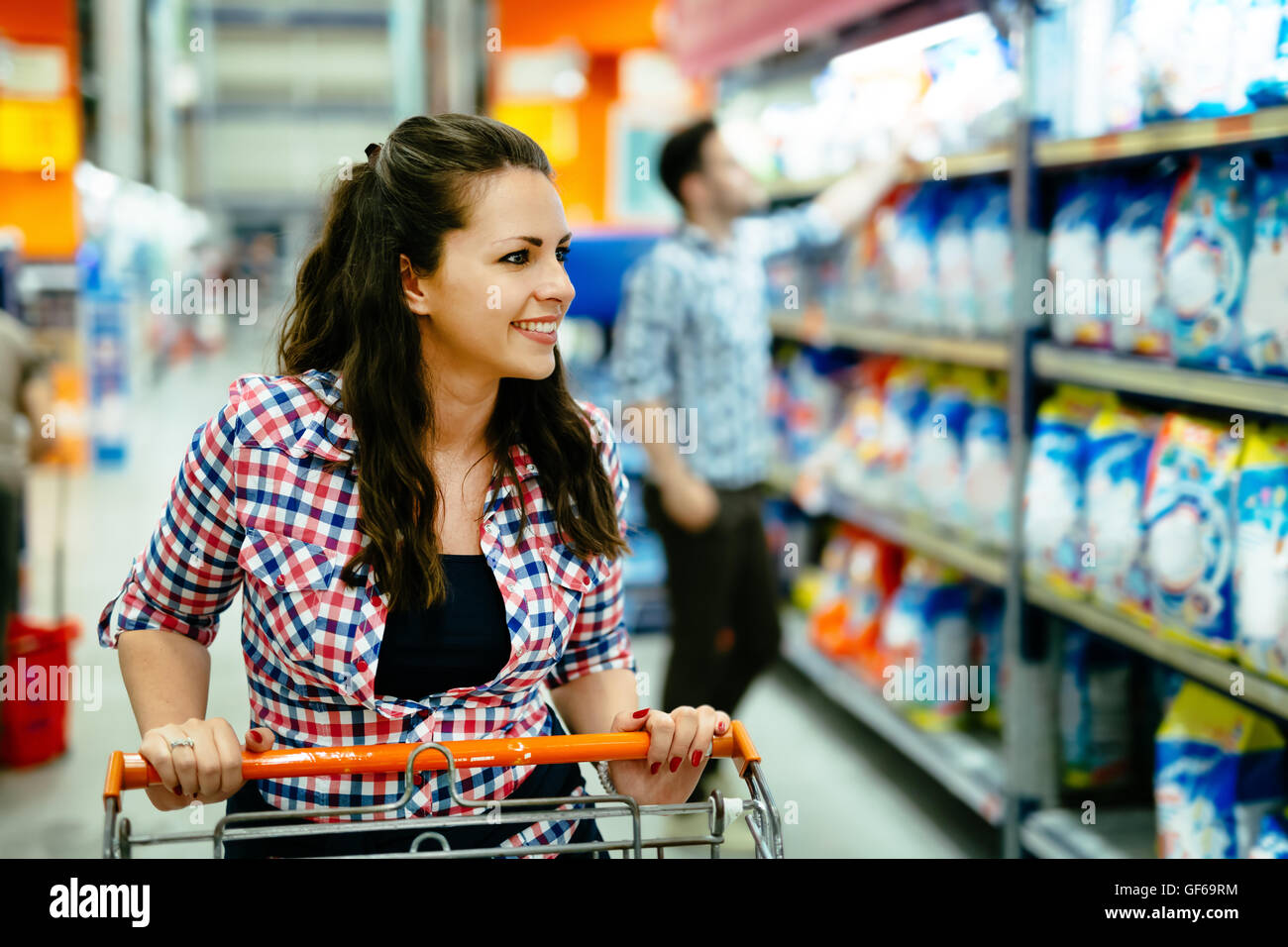 Woman shopping in supermarket and pushing trolley - Stock Image
