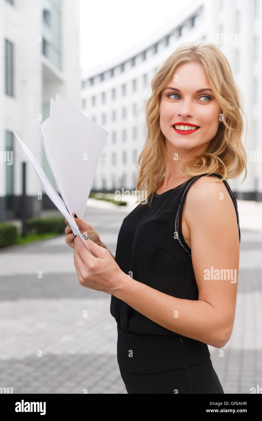 Young curly-headed blond woman with documents smiling on background of new white city buildings - Stock Image