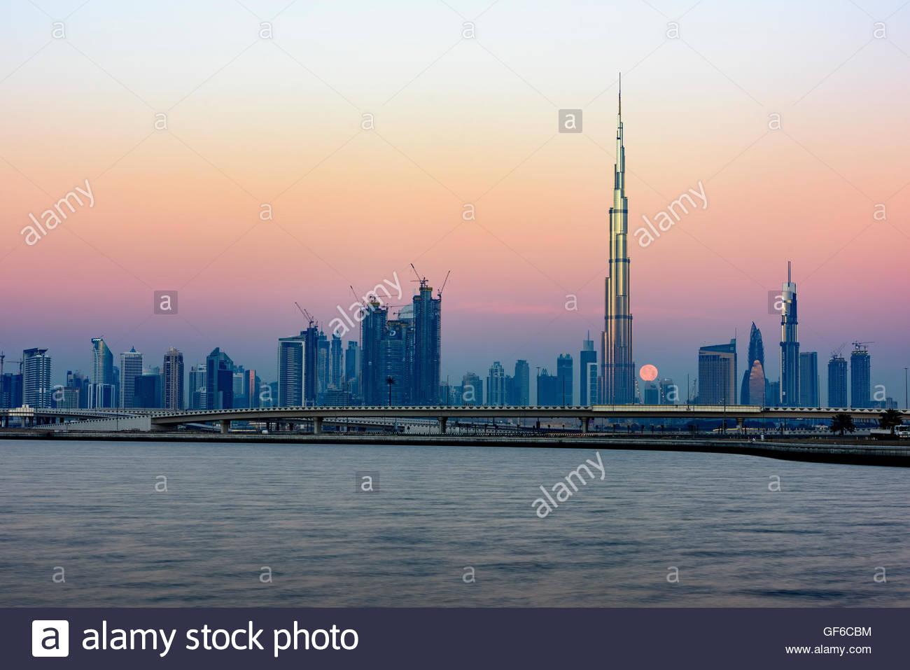 Moon passing behind Burj Khalifa, picture taken early morning from Al Jadaf - Stock Image