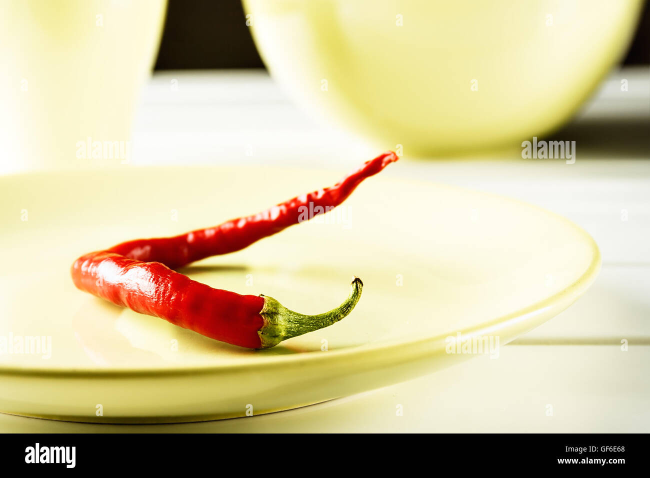 Red hot pepper on green dish over white wood. Horizontal image. - Stock Image
