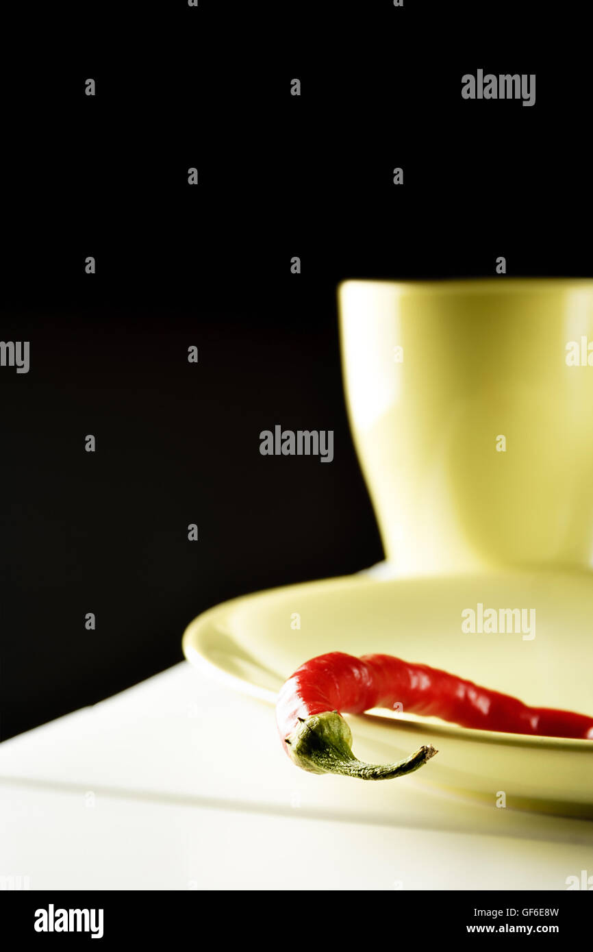 Red hot pepper on green dish over white wood. Vertical image. - Stock Image