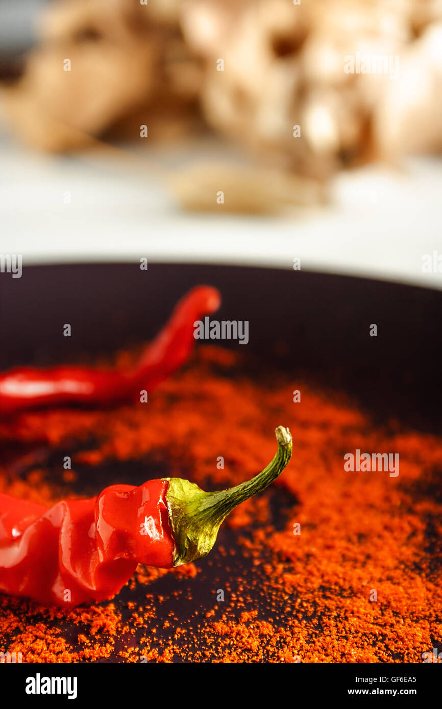 Closeup red pepper with ground paprika on brown dish over white wood. Vertical image. - Stock Image