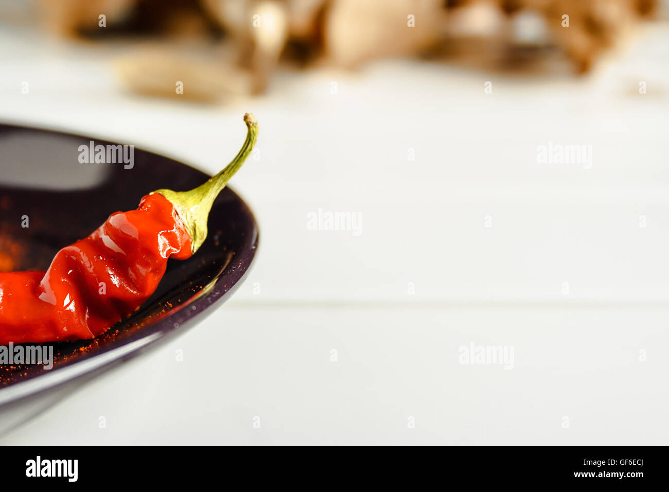 Closeup red pepper on brown dish over white wood. Horizontal image. - Stock Image
