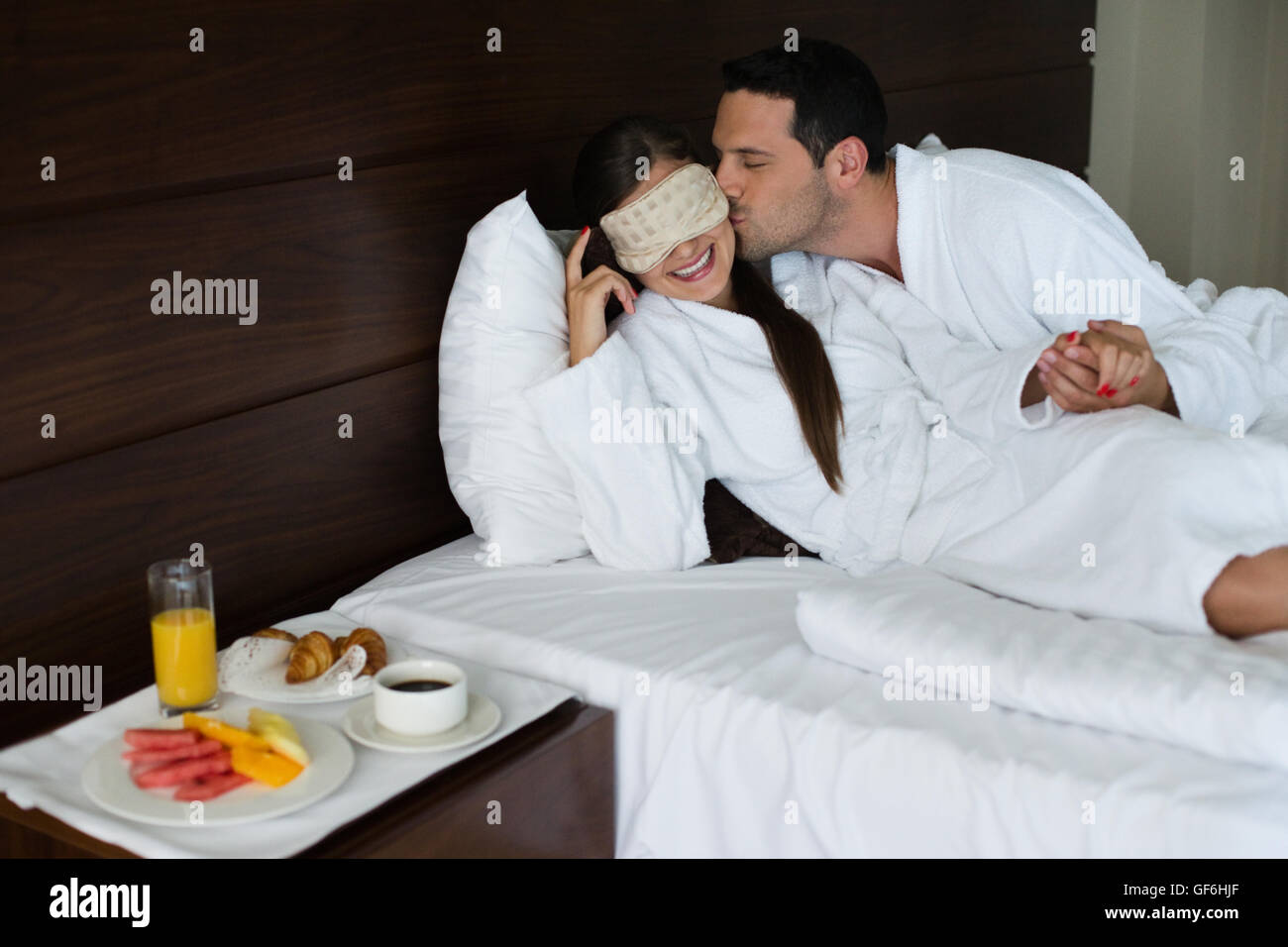 Man kissing woman in hotel room. - Stock Image