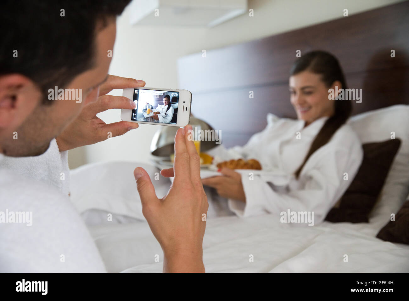 Man taking a photo of woman in hotel room. - Stock Image