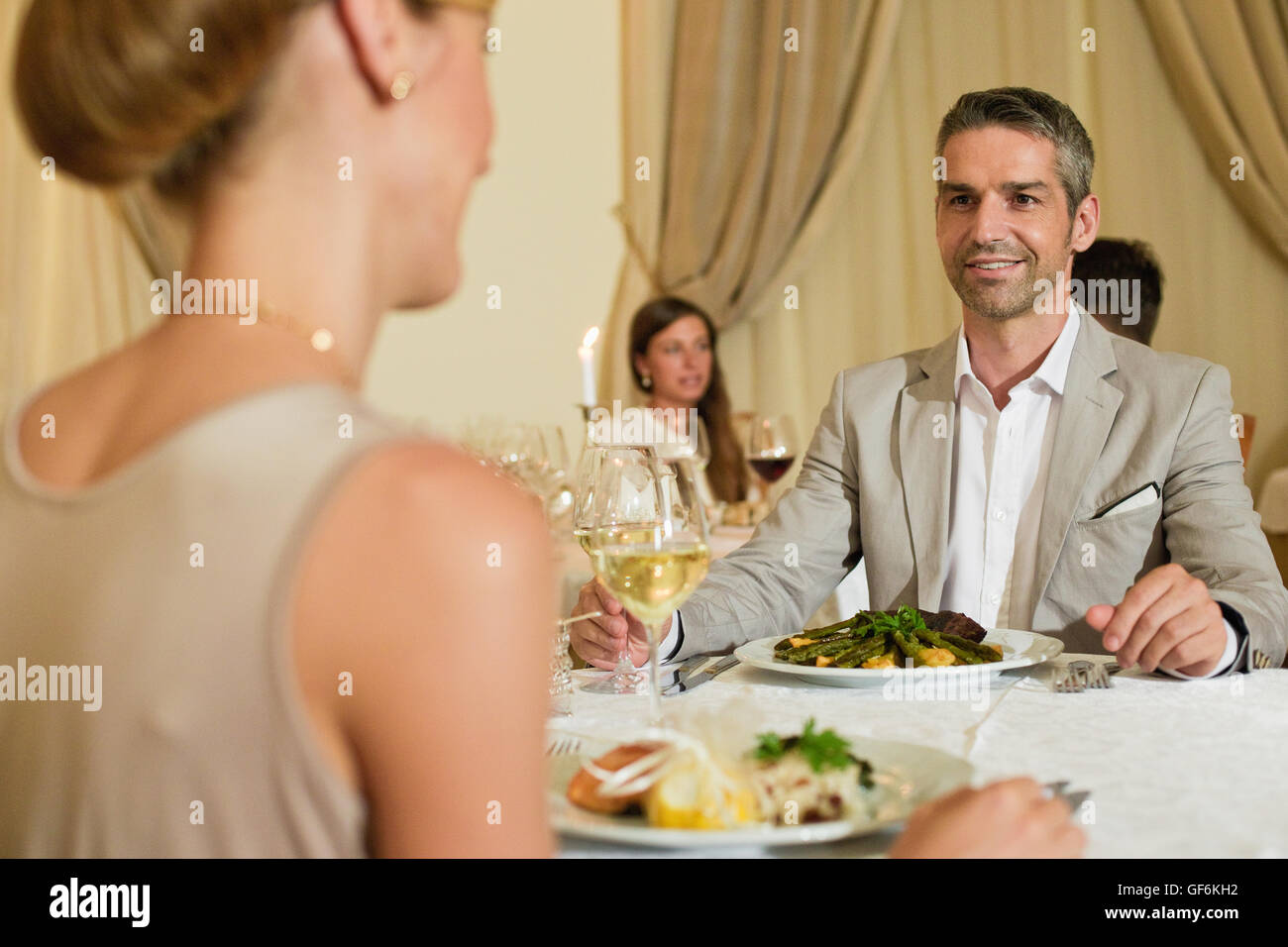 Man and woman sitting in restaurant with people in background. - Stock Image