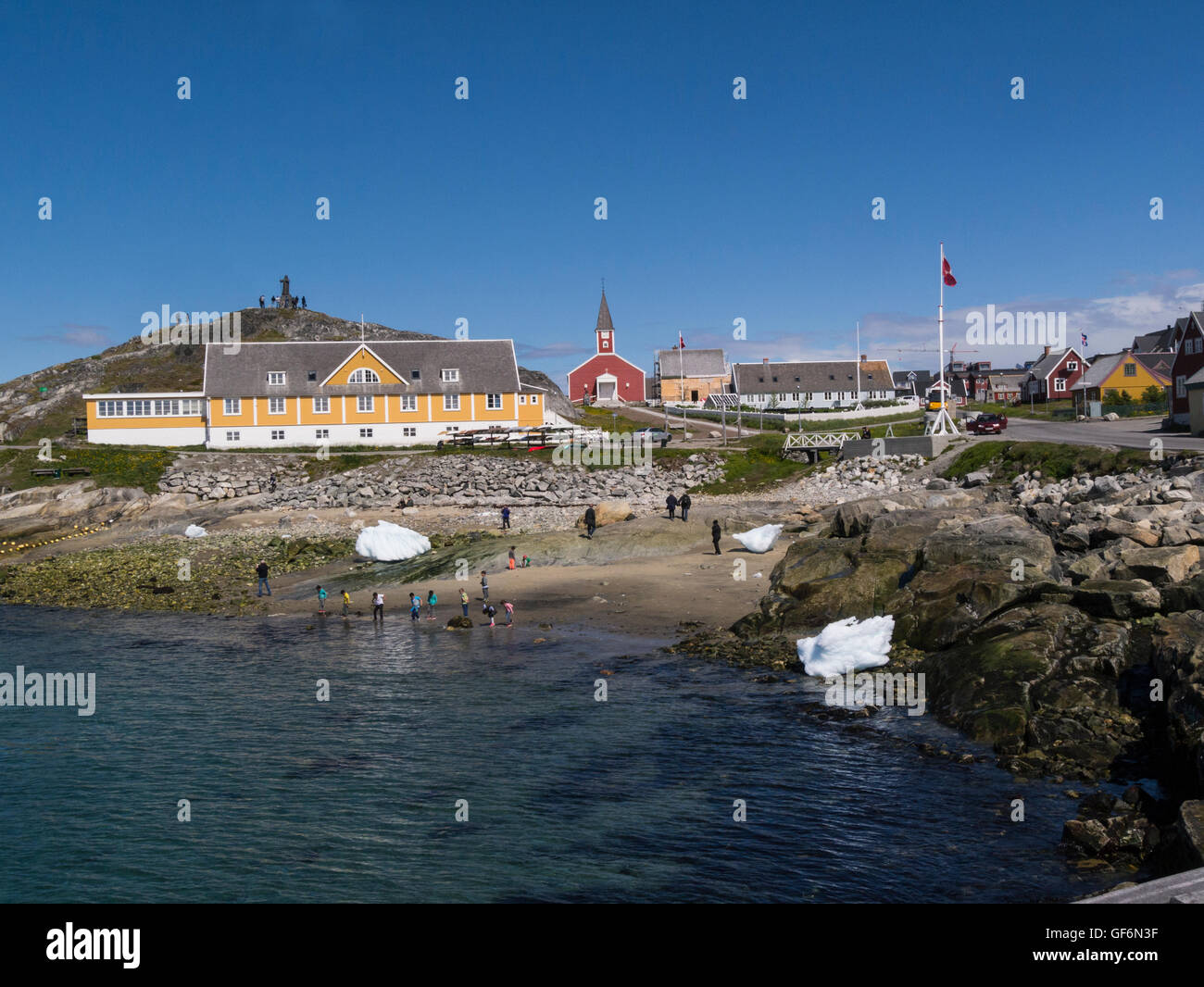 Children playing on beach in historic district Nuuk capital city of Greenland with view Our Saviours church and Stock Photo