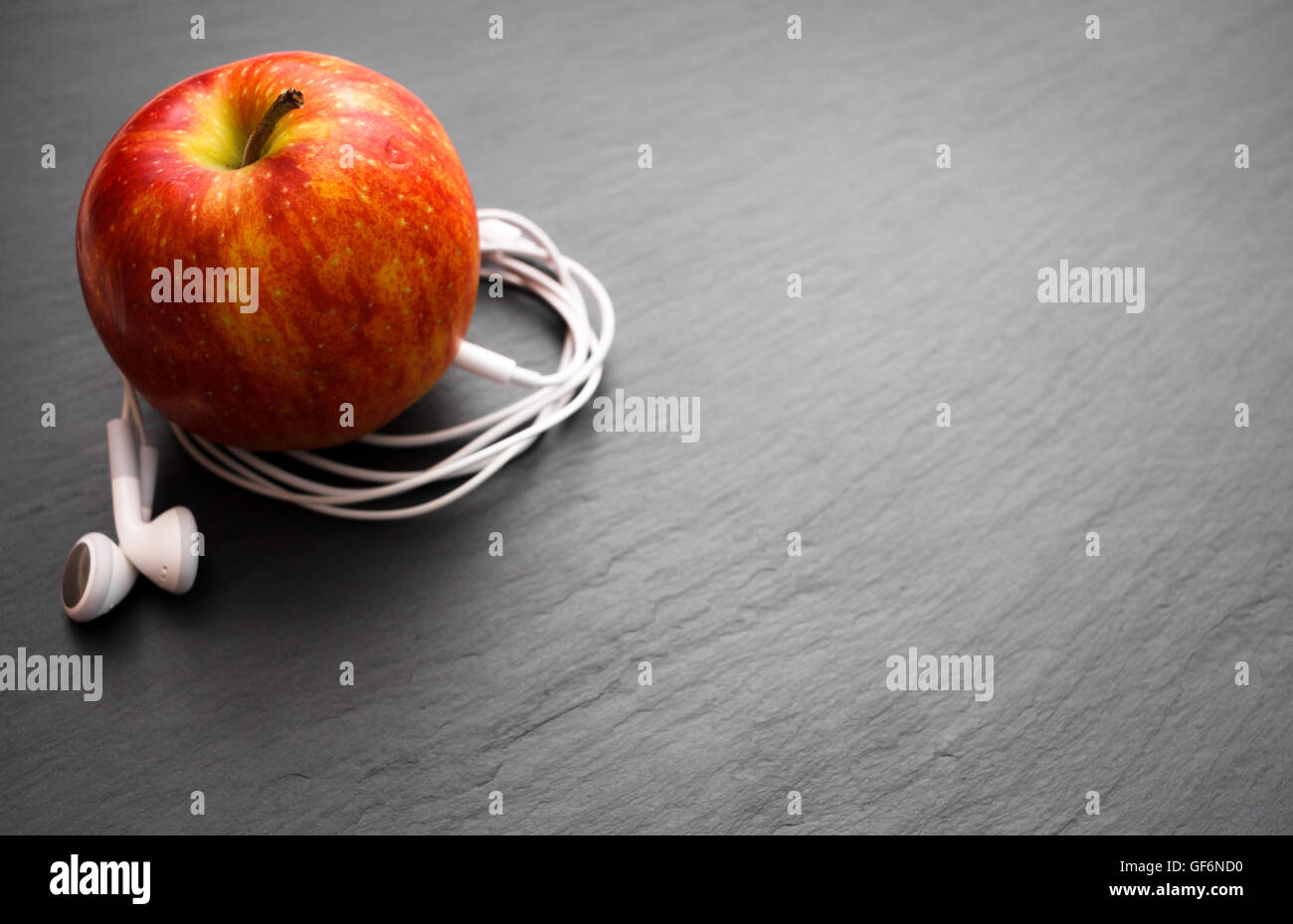 Music playing apple in which earphones are connected - Stock Image