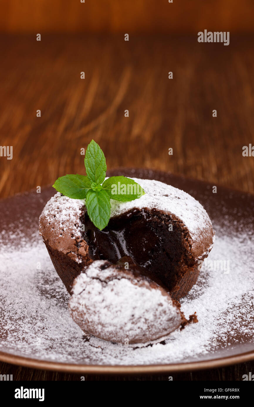 Homemade hot chocolate pudding with fondant center , lava cake on wooden background - Stock Image