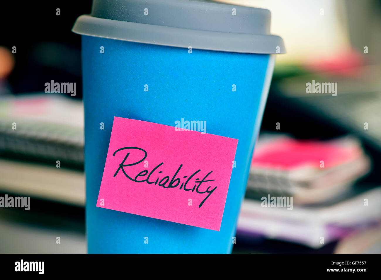closeup of a pink sticky note with the word reliability in a blue cup of coffee or tea on an office desk - Stock Image