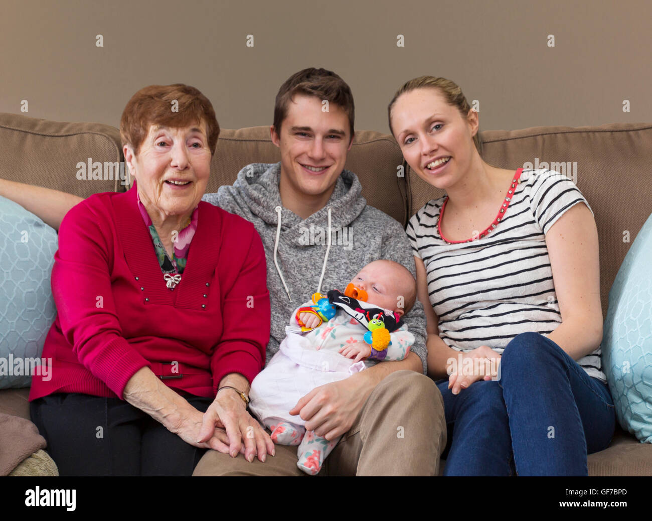 3 generations of people, multi generation of people sitting on sofa with baby - Stock Image
