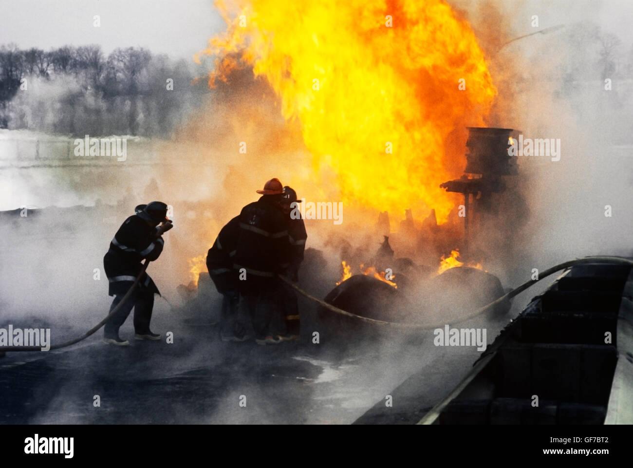 firefighters battle tanker truck fire on highway - Stock Image