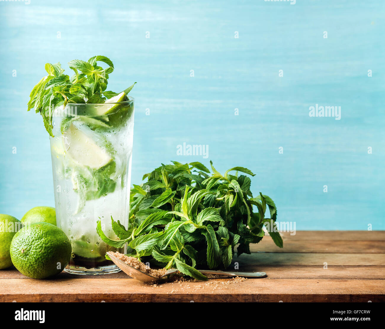 Mojito cocktail in tall glass with mint, brown sugar and limes on a wooden table. Selective focus - Stock Image