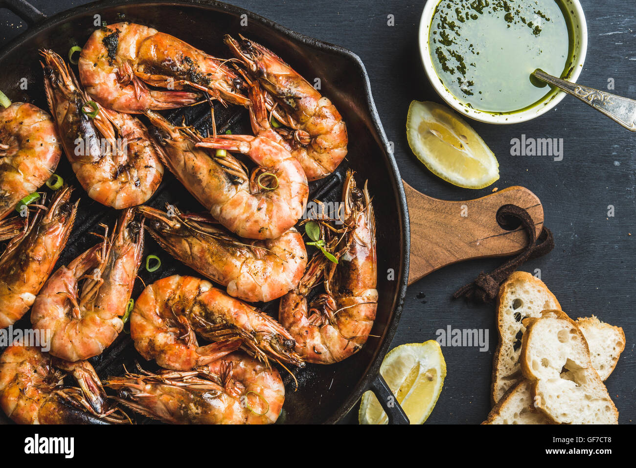 Roasted tiger prawns in iron grilling pan with fresh leek, lemon slices, bread and pesto sauce over black background - Stock Image