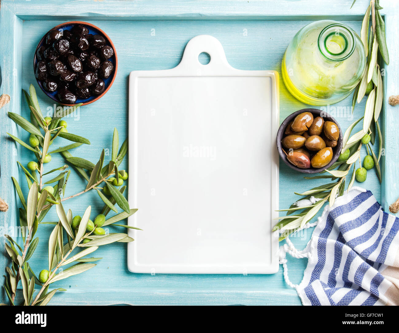 Two bowls with pickled green and black olives, olive tree sprigs, oil in glass bottle, white ceramic board in center. - Stock Image