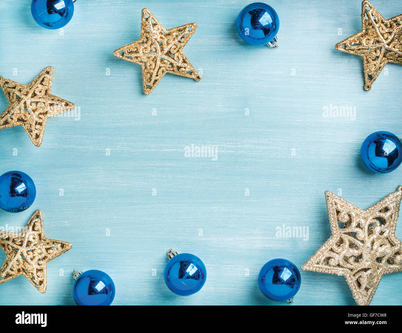 New Year or Christmas background: golden stars and blue glass balls over turquoise wooden backdrop, copy space Stock Photo