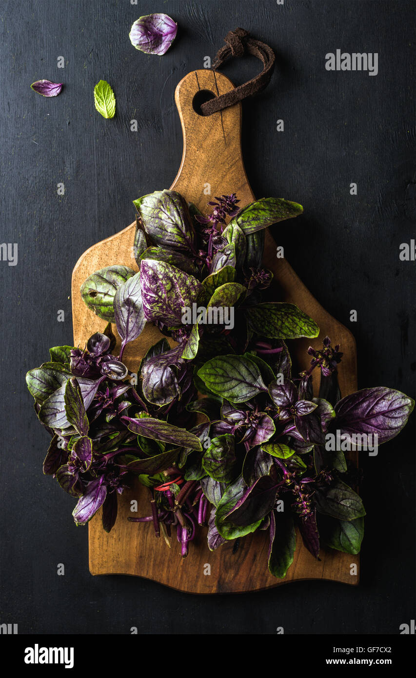 Violet basil bunch on wooden chopping board - Stock Image