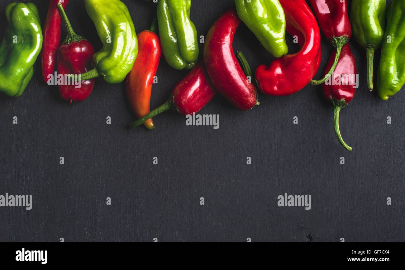 Colorful hot chili peppers on black wooden background, copy space - Stock Image