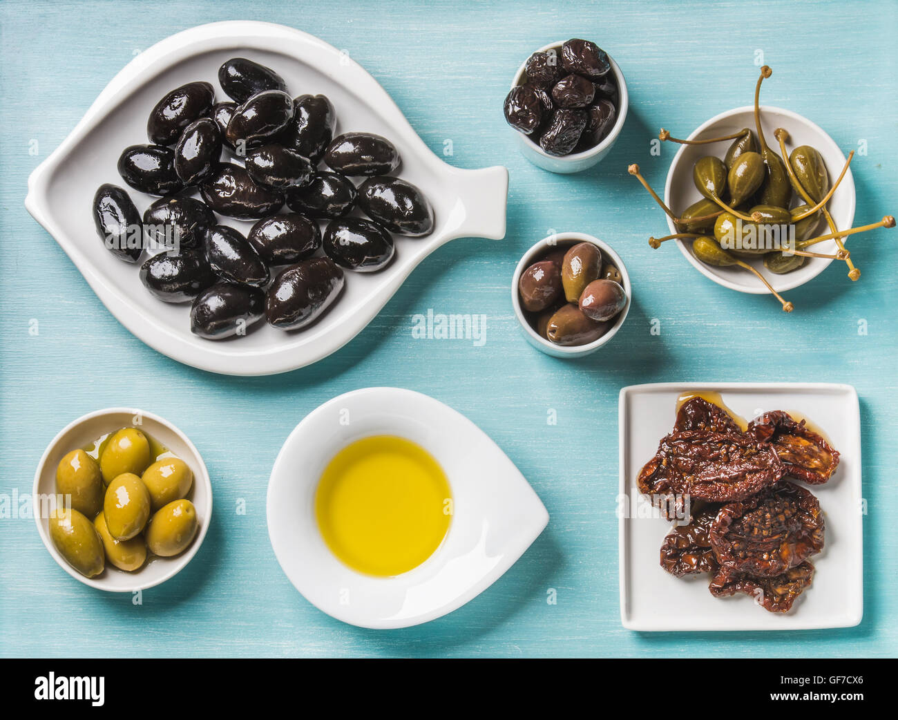 Mediterranean snack assortment. Black and green Greek olives, capers, olive oil, sun-dried tomatoes over turquoise - Stock Image