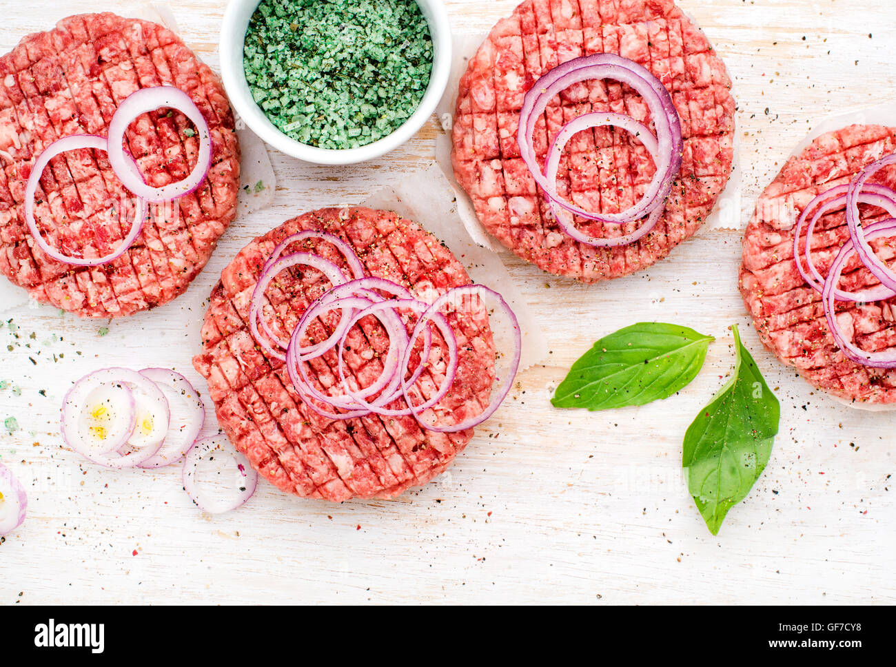 Raw ground beef meat cutlet for cooking burgers with onion rings and spices on white wooden background - Stock Image