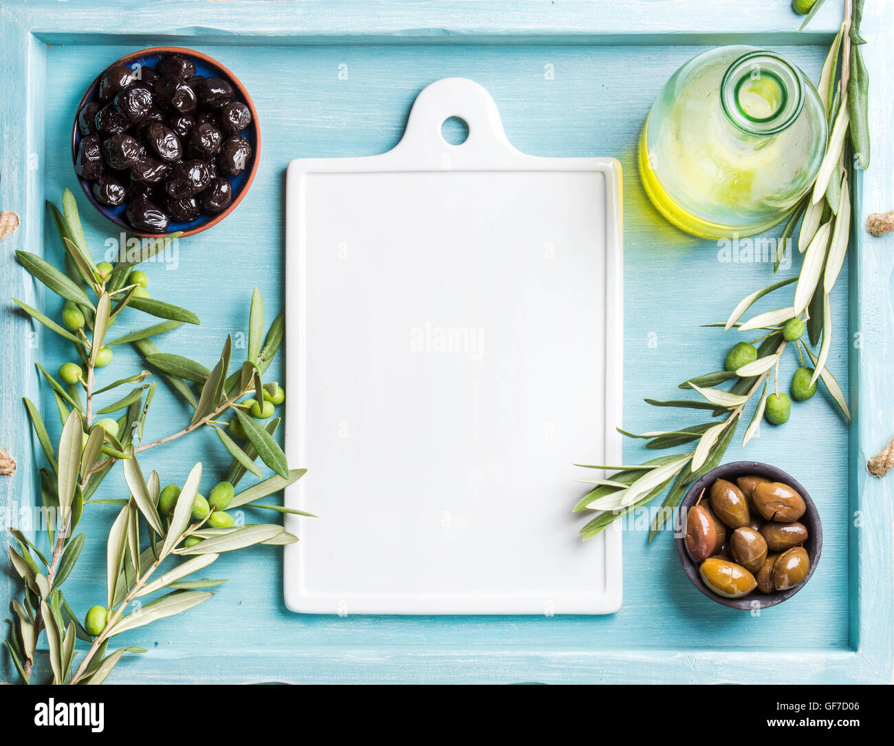 Two bowls with pickled green and black olives, olive tree sprigs, oil, white ceramic board in center. Copy space. - Stock Image