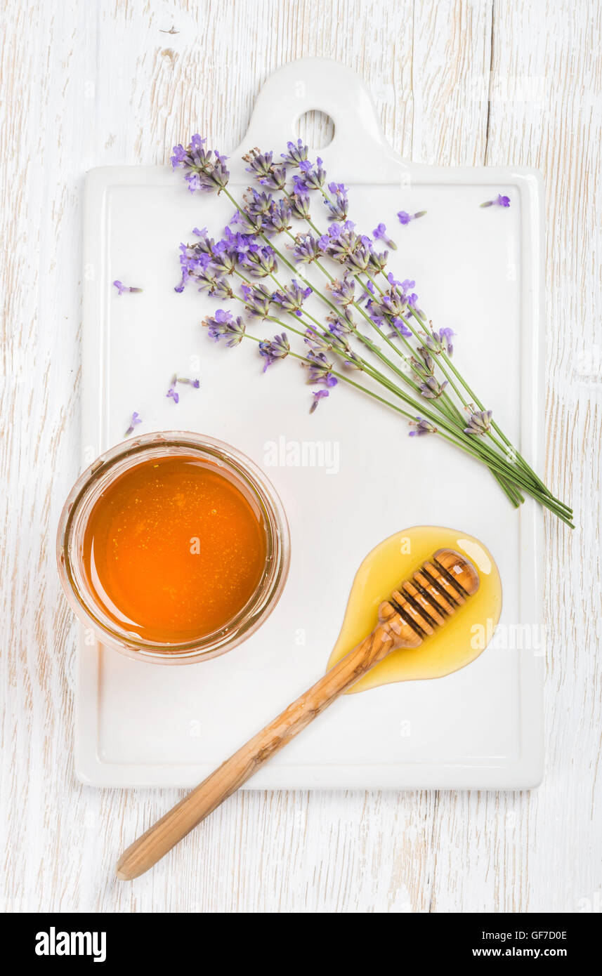 Lavender honey in glass jar with flowers on white background - Stock Image