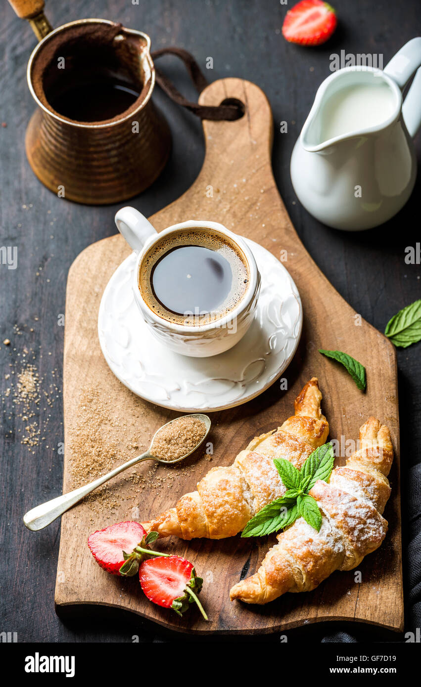 Breakfast set. Freshly baked croissants with strawberry, mint leaves and cup of coffee on wooden board over dark - Stock Image