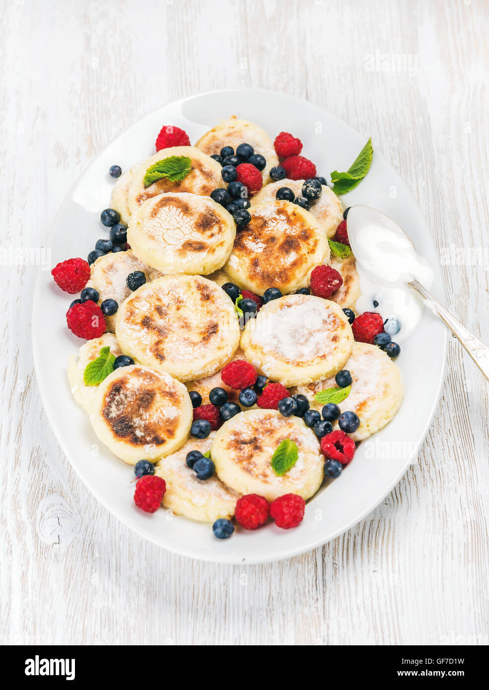 Syrniki or cottage cheese pancakes with fresh forest berries and sour cream sauce in serving dish over white wooden - Stock Image