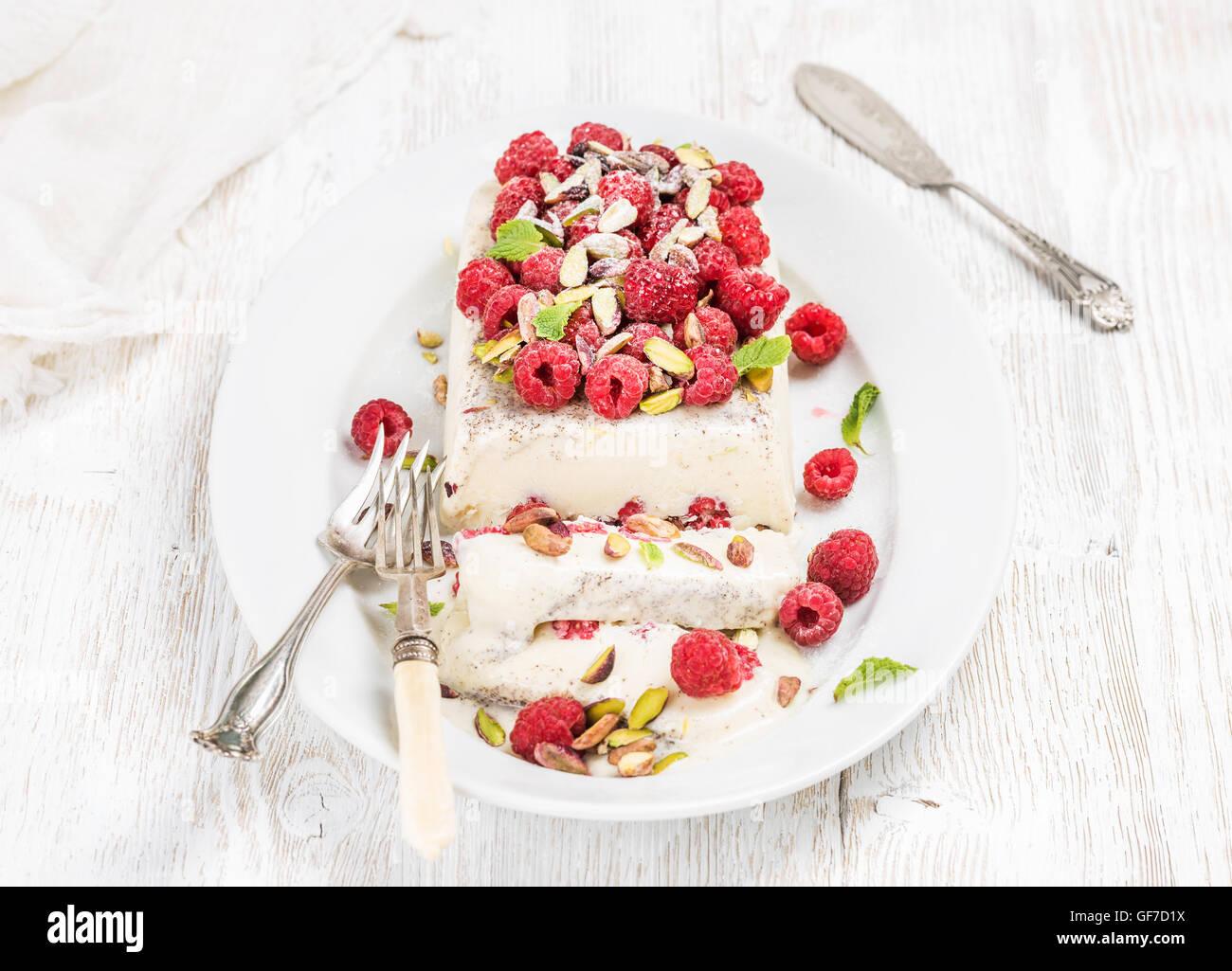 Homemade semifreddo with pistachio, raspberries and mint leaves - Stock Image