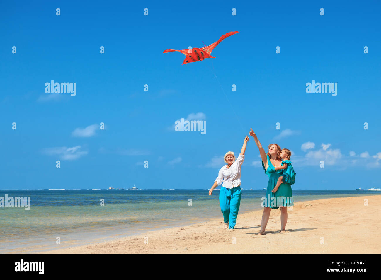 Happy family has fun on beach - grandmother, mother and baby girl walk along ocean surf. Senior woman runs with - Stock Image