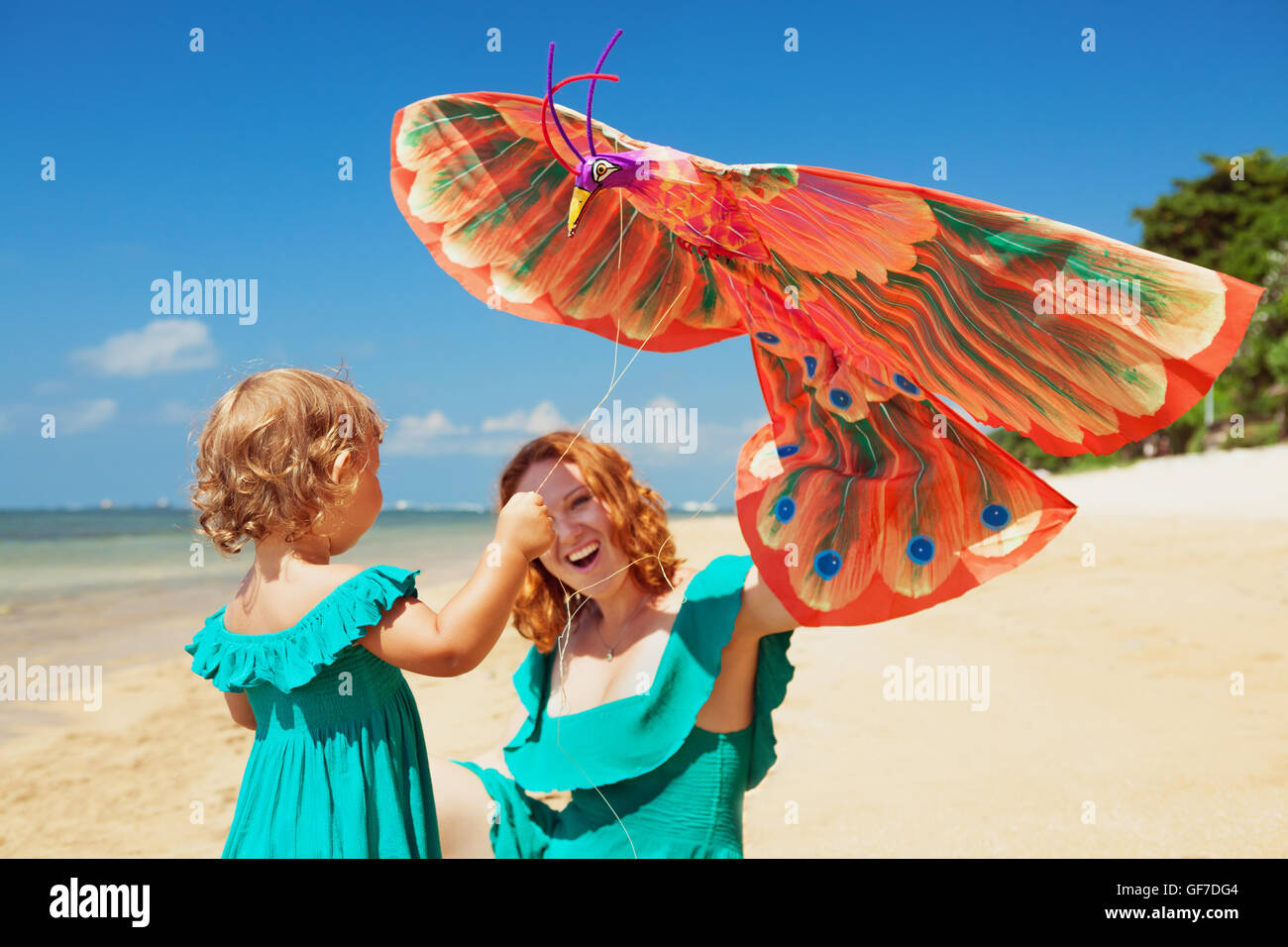 Happy family has fun on sunny sand beach - mother and baby girl walk together along ocean surf and launch traditional - Stock Image