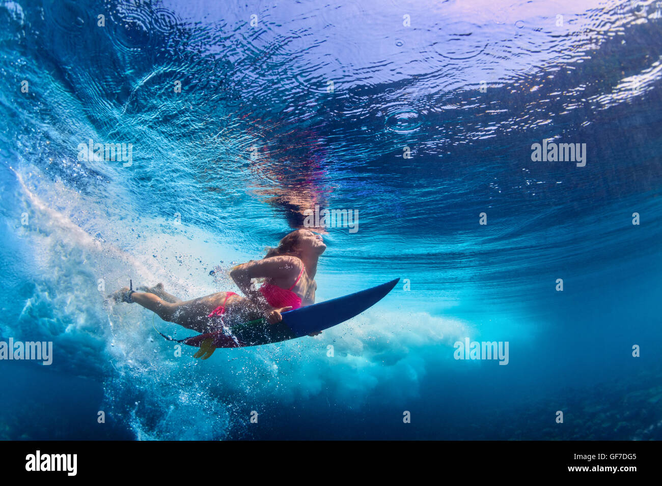 Young active girl wearing bikini in action - surfer with surf board dive underwater under big atlantic ocean wave. - Stock Image