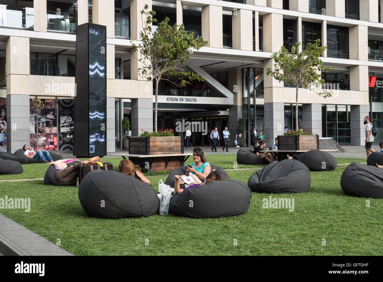 People relaxing on bean bags, Takutai Atrium, Galway Street Auckland, North Island, New Zealand. - Stock Image