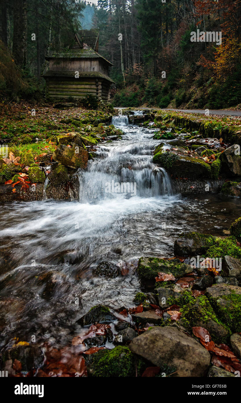 mountain river with stones and moss in the forest near the abandoned wooden house near the hillside - Stock Image