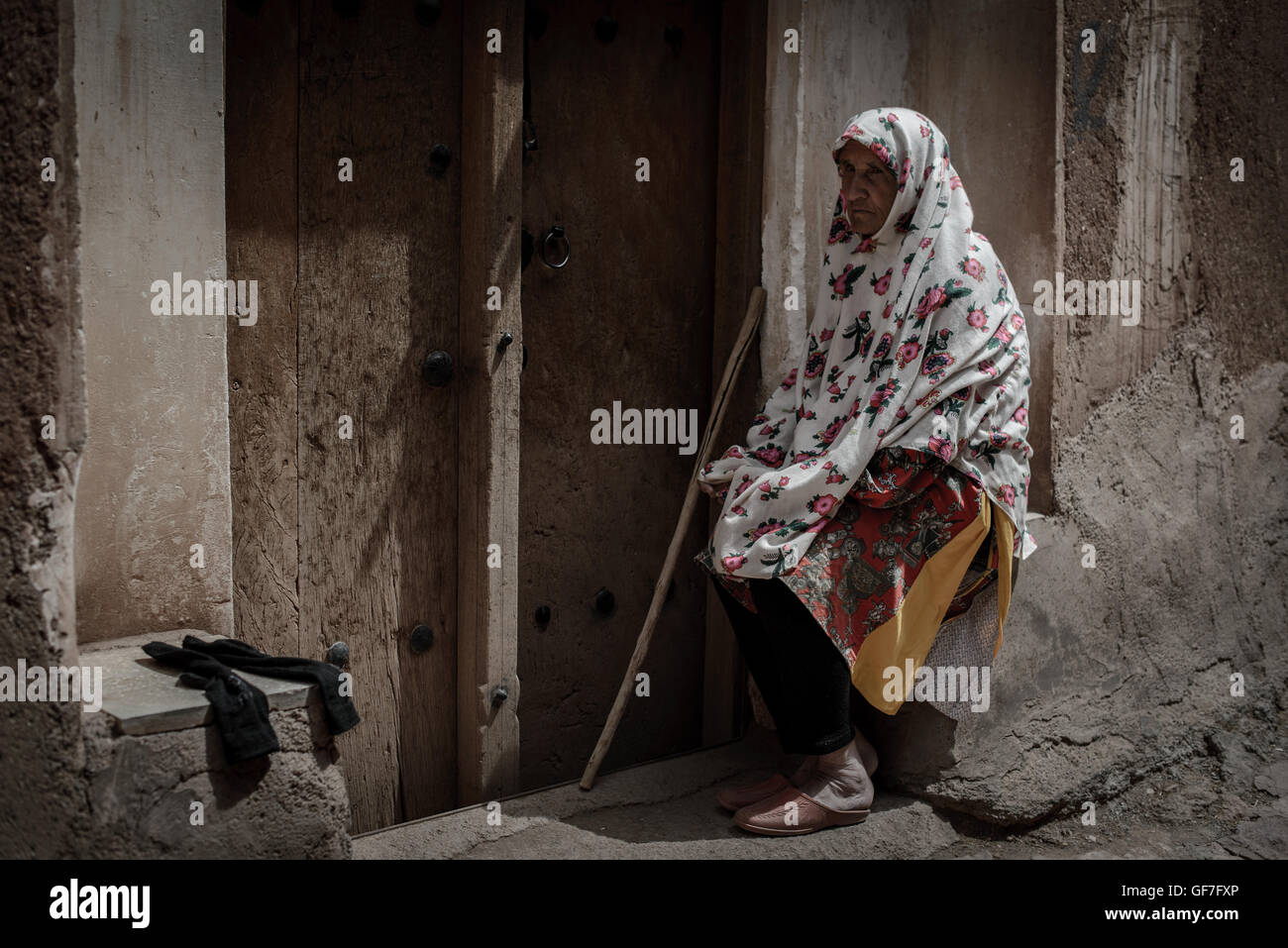 Local elderly woman in front of her home in Abyaneh village near Kashan, Iran - Stock Image